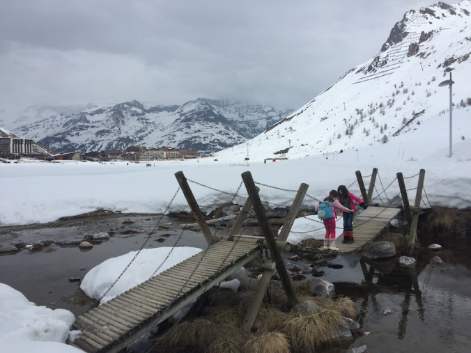 Two girls play on a wobbly wooden bridge over a stream in a snowy landscape, with snow covered mountains around and a town in the distance